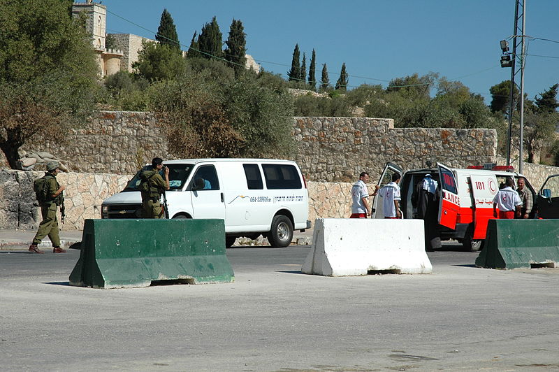 An red ambulance being searched by soldiers in green uniform, behind concrete barriers