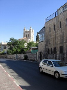 Photo of a street with a car passing and a neo-Romanesque square church tower in the background