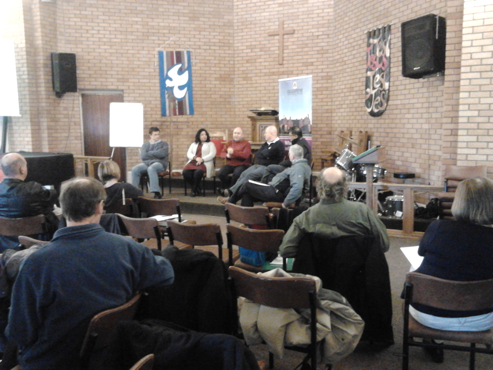 A group of people in a discussion panel with audience watching