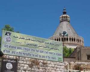 Church building, with banner in front reading 'And whoever seeks a religion other than Islam, it will never be accepted of him, and in the Hereafter he will be one of the losers'